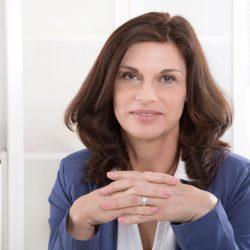 Female senior manager sitting at desk.